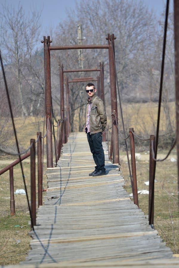 Homme sur un pont suspendu image stock