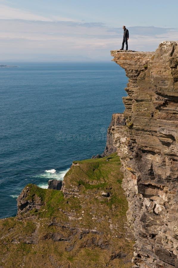 Homme sur une falaise image stock