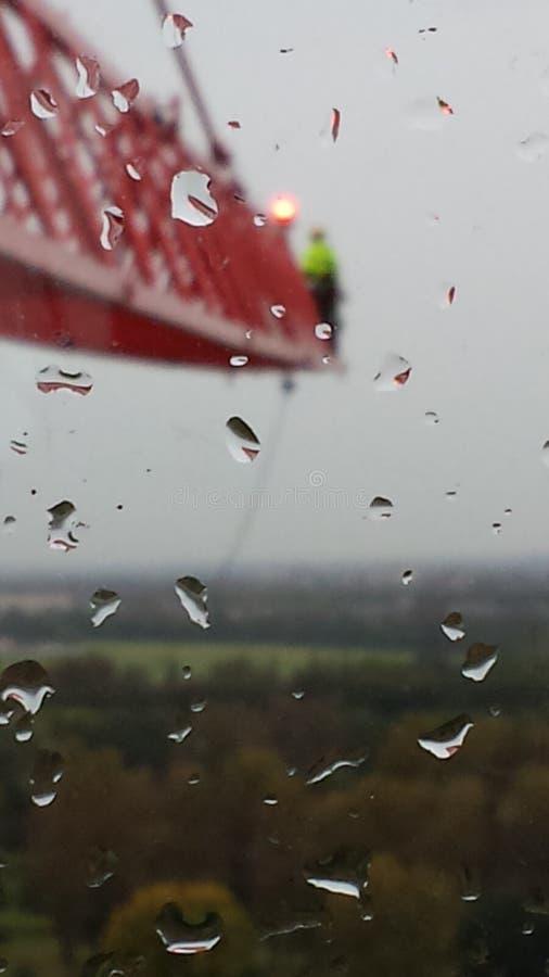 Homme sur une potence avant d'une grue à tour dans un jour pluvieux à Londres image libre de droits