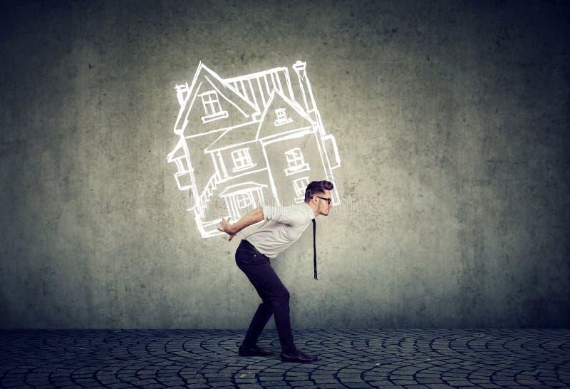 Homme surchargé d'affaires portant une maison photo libre de droits