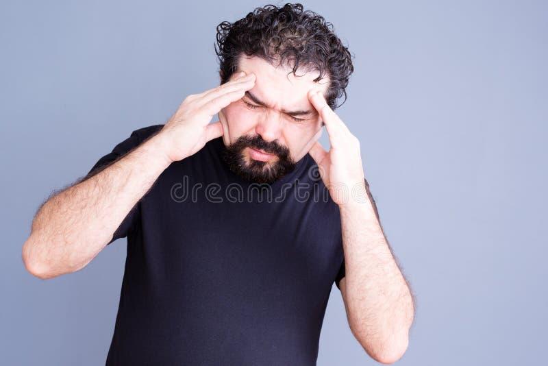 Homme surchargé frottant son front photos stock
