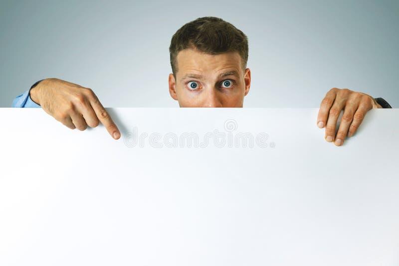 Homme surpris pointant sur une affiche blanche avec espace de copie photos stock