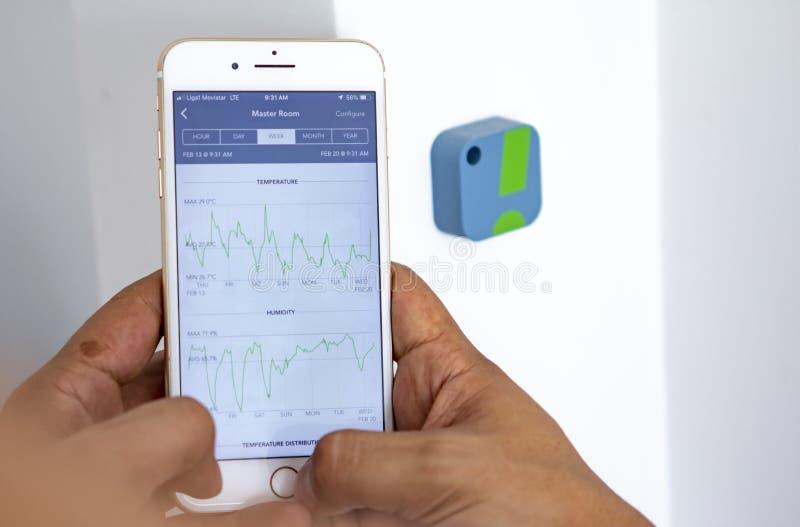 Homme surveillant les niveaux à la maison d'humidité avec l'appli image stock