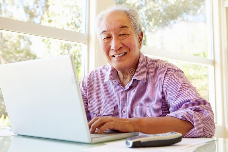 Homme taiwanais supérieur travaillant sur l'ordinateur portable images stock