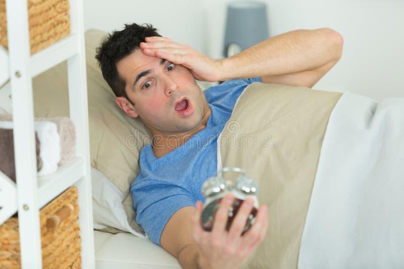 Homme tard dans le lit avec l'alarme photographie stock