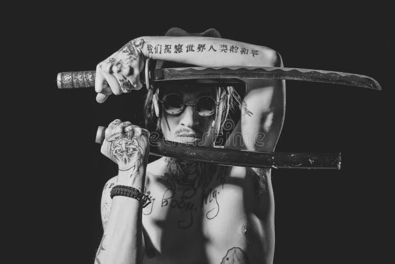Homme tatoué des Yakuza Équipez la pose avec l'épée avec les mains, le cou et le coffre tatoués images libres de droits