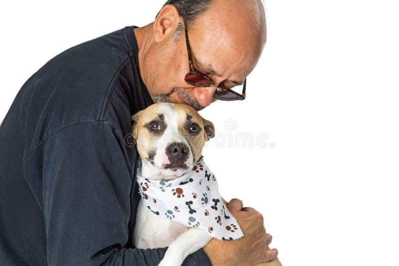 Homme tenant affectueusement le chien effrayé de délivrance image stock
