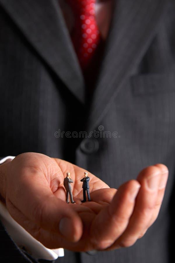 Homme tenant Businessmen In Palm modèle de main photos libres de droits