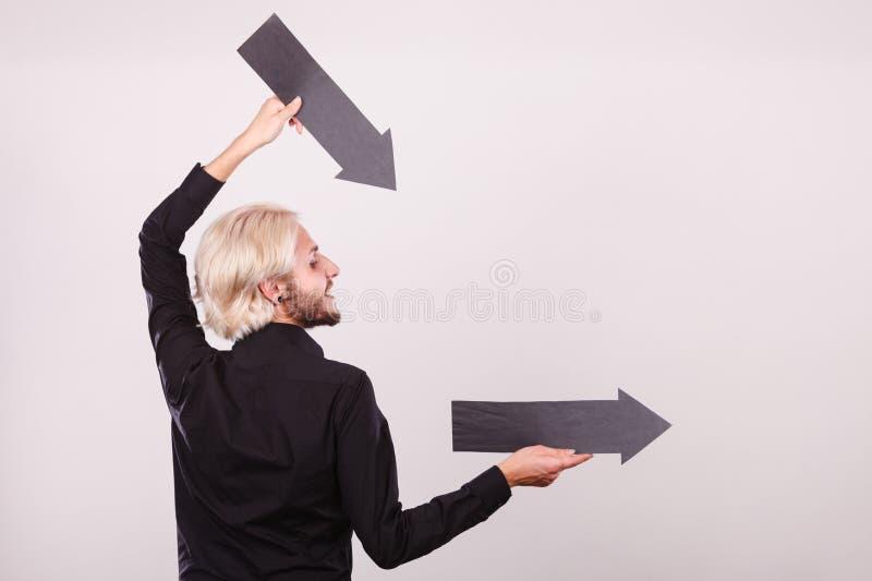 Homme tenant deux flèches dirigeant la même direction photo libre de droits