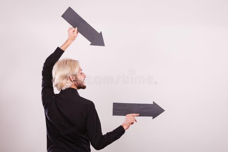 Homme tenant deux fl?ches dirigeant la m?me direction image libre de droits