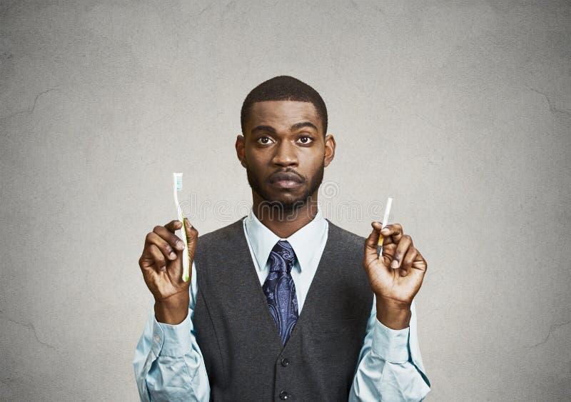 Homme tenant la cigarette et la brosse à dents photographie stock