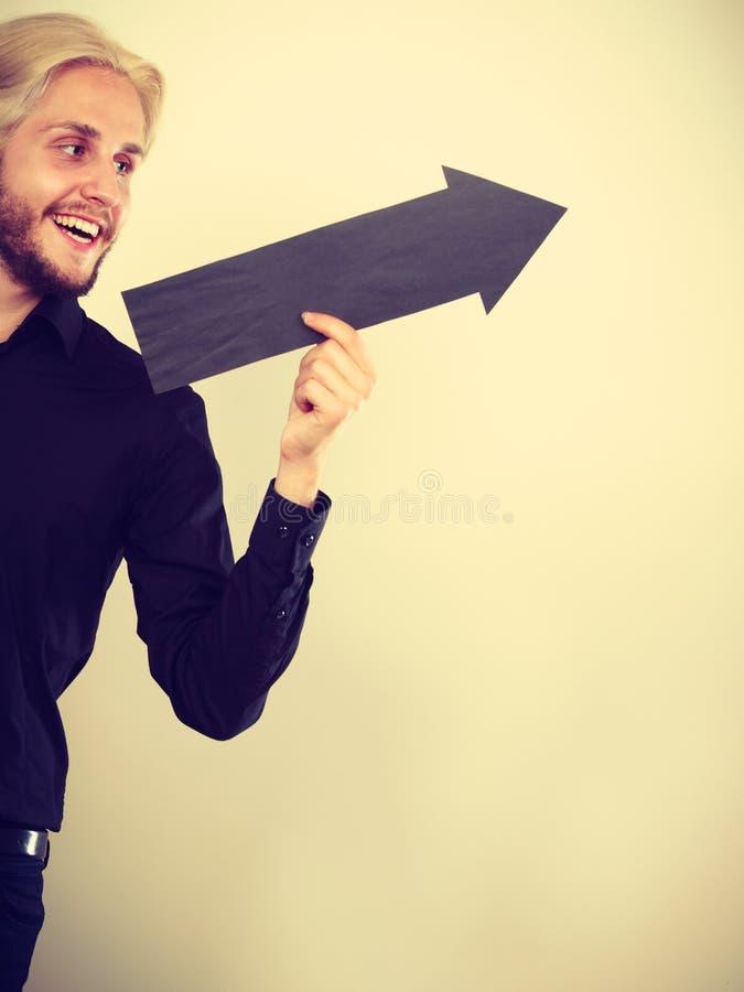 Homme tenant la flèche noire se dirigeant juste image stock