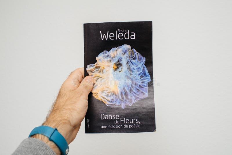 Homme tenant la magazine d'examen de Weleda photo stock