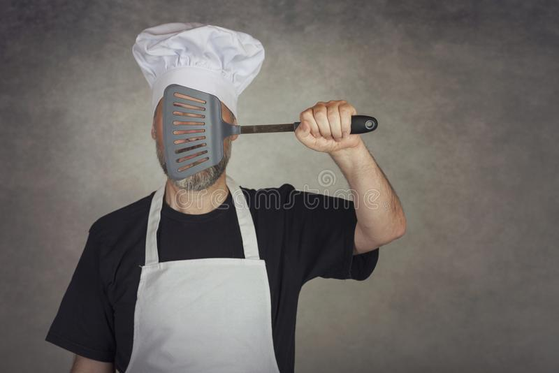 Homme tenant la spatule dans ses yeux photos stock