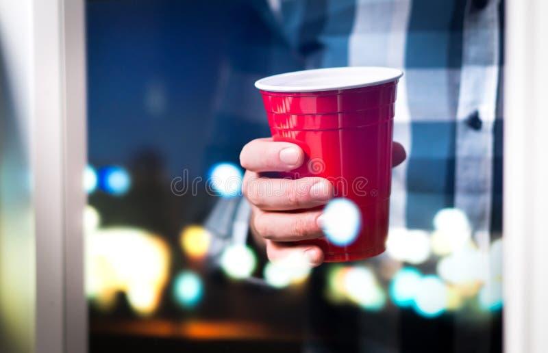 Homme tenant la tasse rouge en partie de luxe ou d'université photo stock