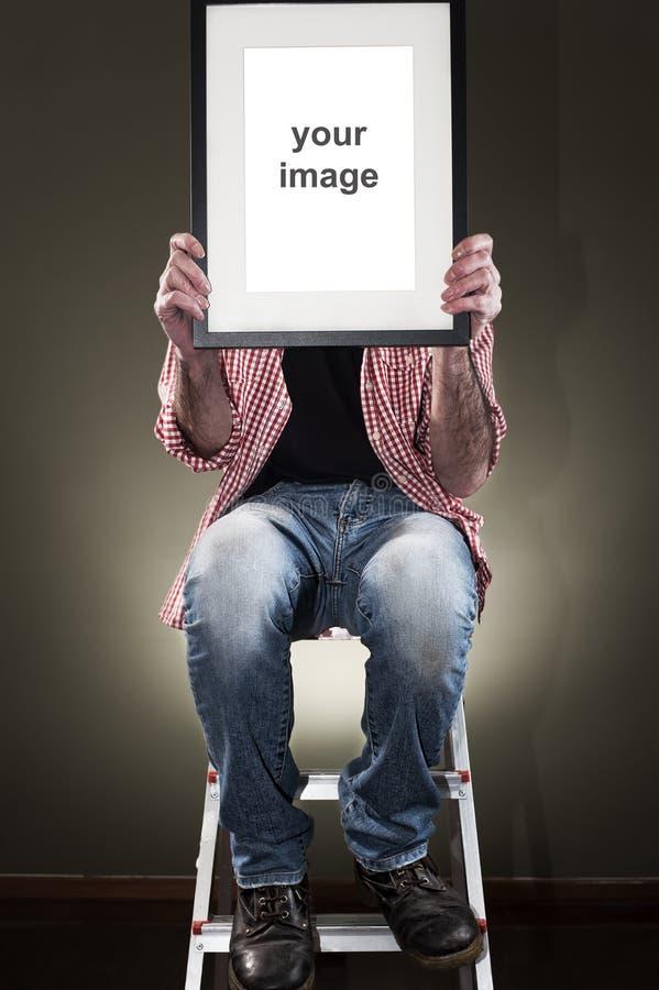 Homme tenant le cadre de tableau photo stock