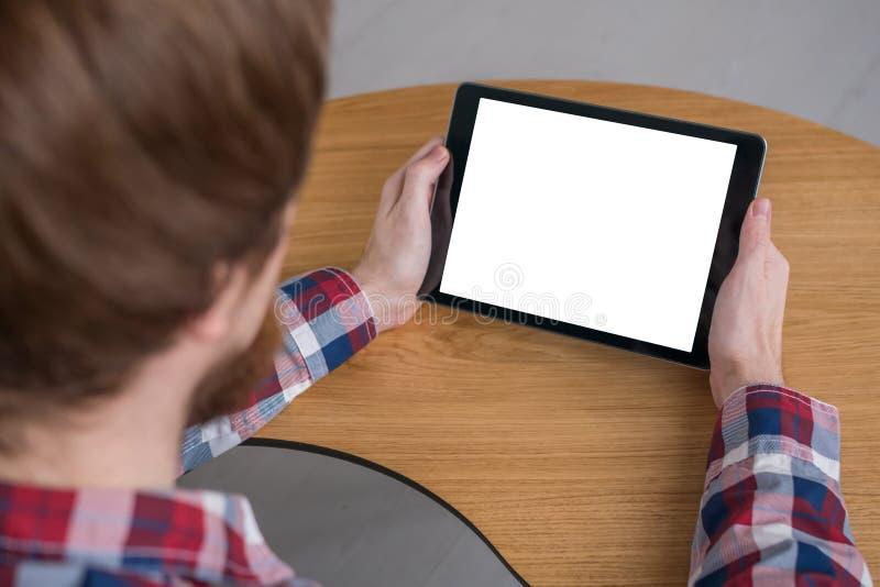Homme tenant le dispositif numérique noir de comprimé avec l'écran vide blanc - image de maquette photo stock