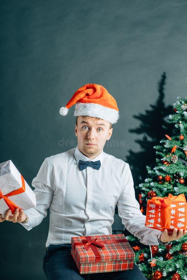 Homme tenant le giftbox Le mâle beau avec le boîte-cadeau remet dedans l'arbre de Noël images stock