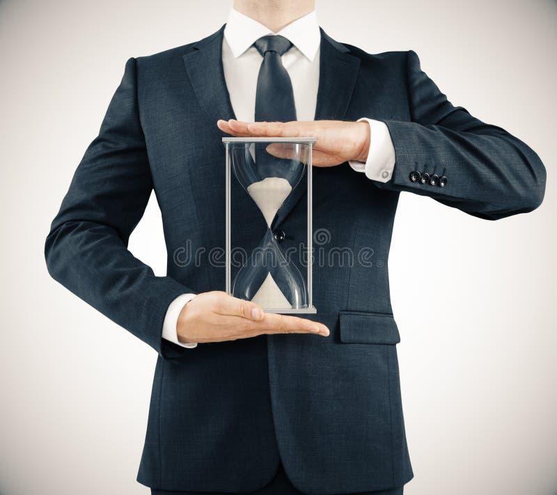 Homme tenant le sablier, concept de temps illustration stock