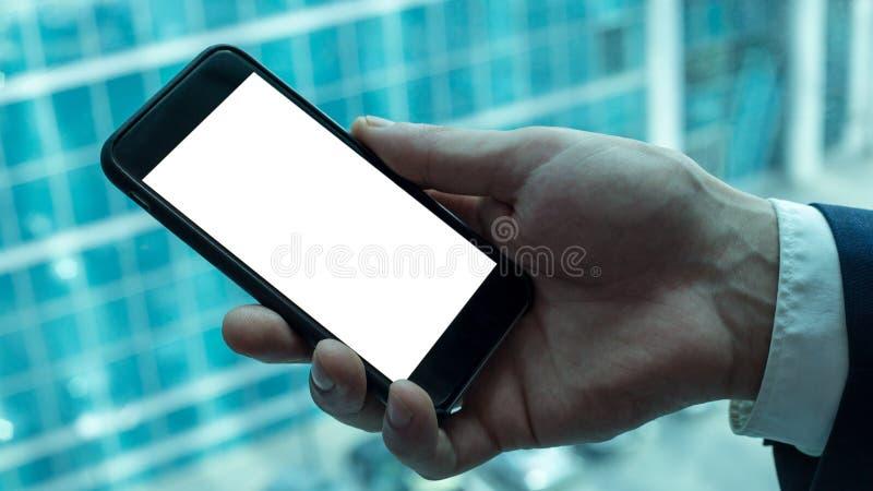 Homme tenant le smartphone noir près de la fenêtre image stock