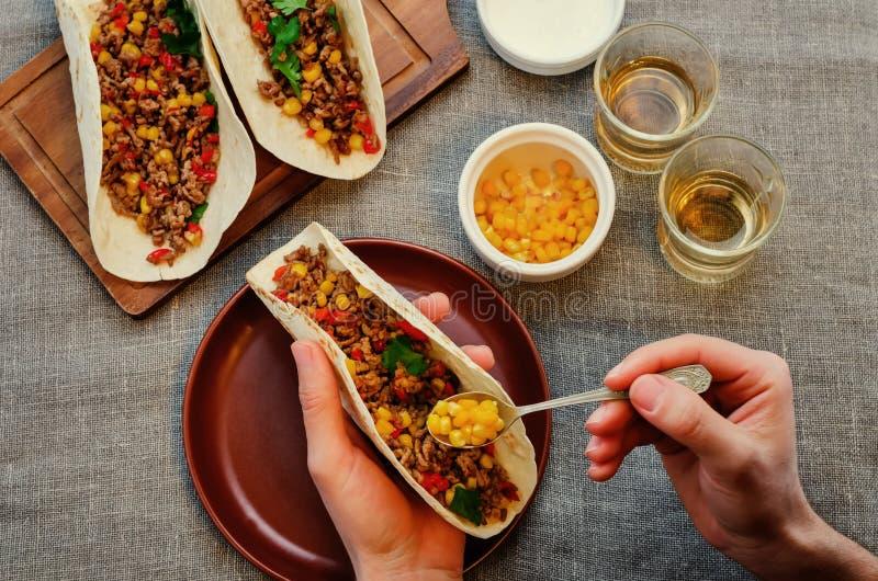 Homme tenant le tacos avec de la viande, maïs image stock