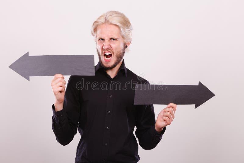 Homme tenant les flèches noires se dirigeant à gauche et à droite photographie stock libre de droits