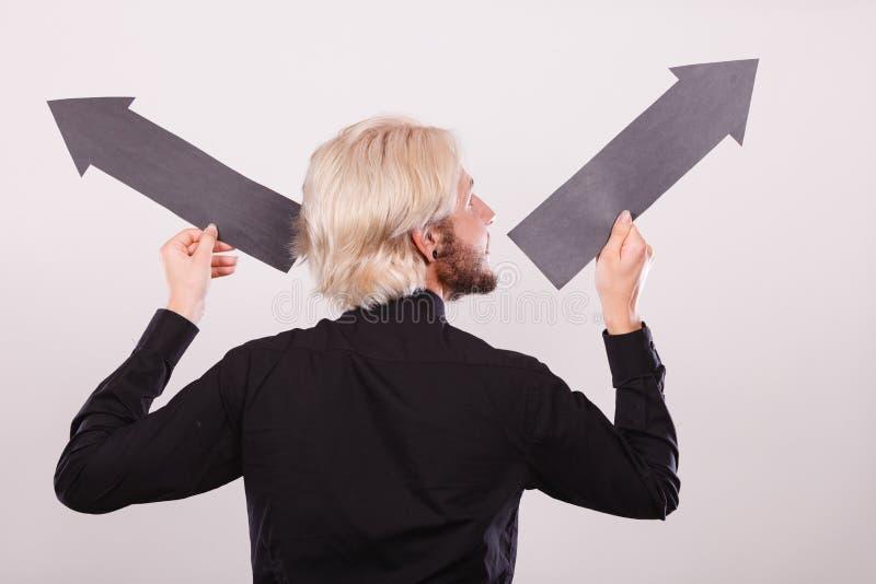 Homme tenant les flèches noires se dirigeant à gauche et à droite photographie stock