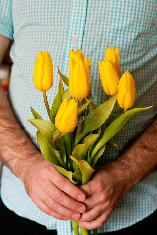 Homme tenant les tulipes jaunes Jour de mères, concept du jour des femmes photographie stock libre de droits