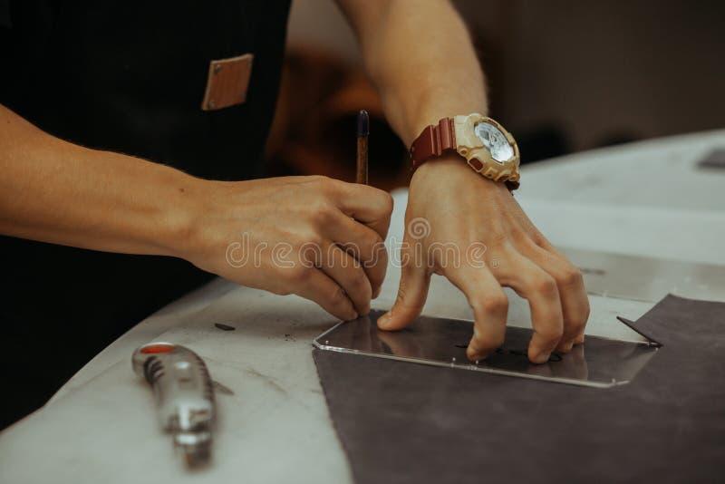 Homme tenant ouvrer l'outil et le travail Fermez-vous d'un maître fonctionnant avec le textile en cuir à son atelier utilisant de images stock