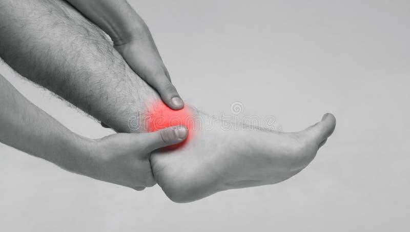 Homme tenant sa cheville en douleur, photo monochrome image stock