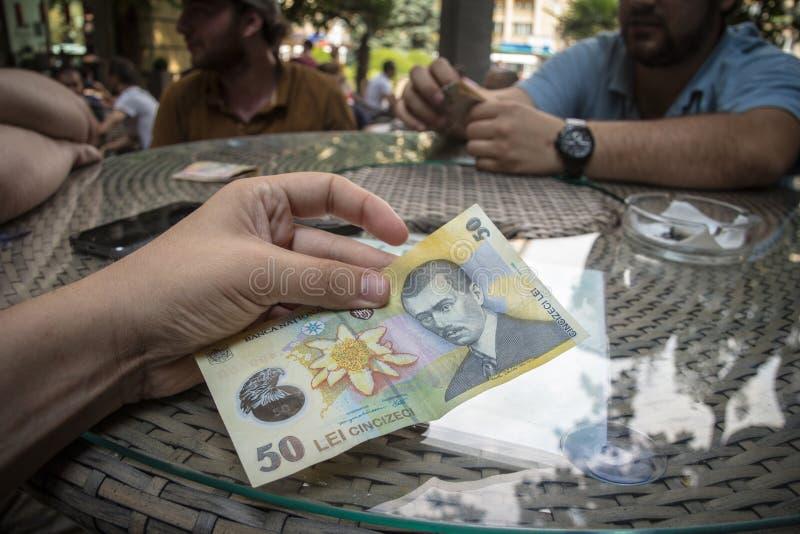 Homme tenant un banknot roumain de 50 leu sur une table Aussi bien RON appelé, Lei, ou le leu, est la devise officielle de la Rou images stock