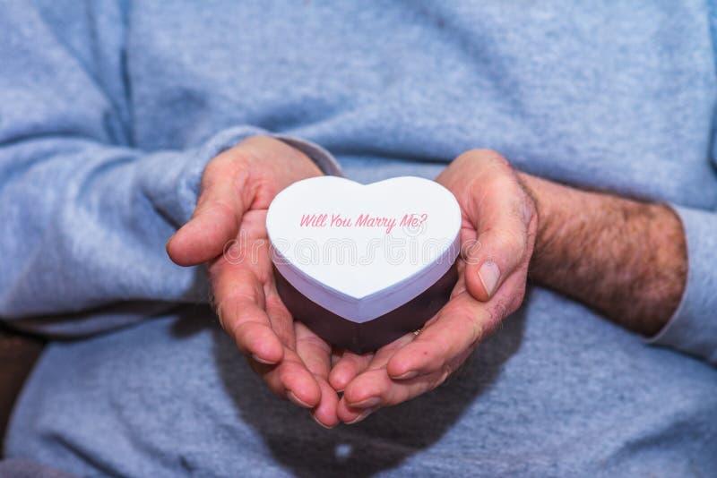 Homme tenant un boîte-cadeau en forme de coeur photographie stock