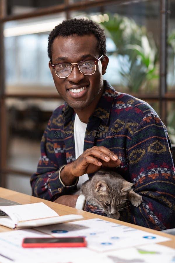 Homme tenant un chat sur son lieu de travail photo stock