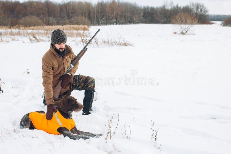 Homme tenant une arme à feu et choyant le chien photos libres de droits