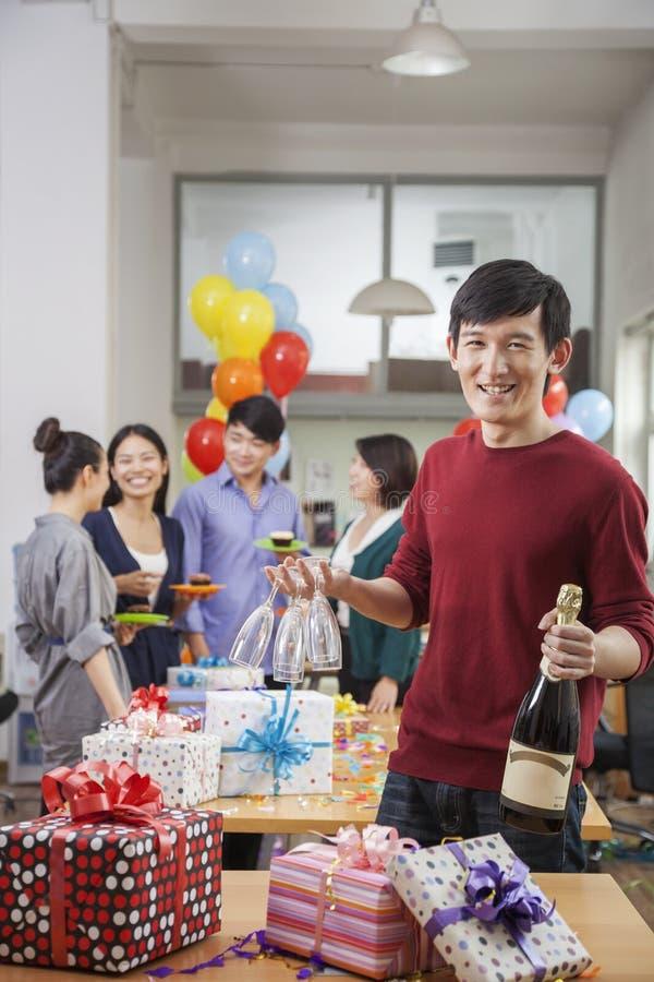 Homme tenant une bouteille de Champagne et des verres à la fête au bureau images libres de droits