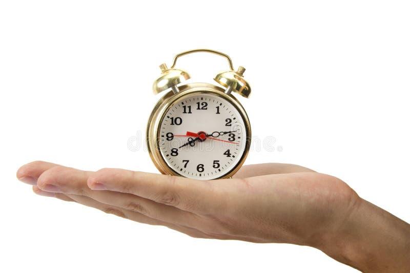 Homme tenant une horloge dans sa main. photos stock