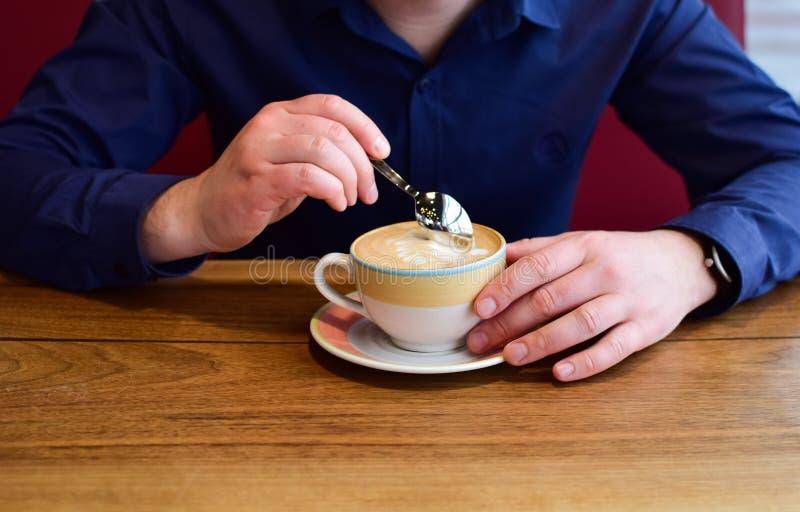 Homme tenant une tasse de cappuccino images libres de droits