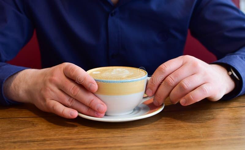 Homme tenant une tasse de cappuccino photographie stock libre de droits