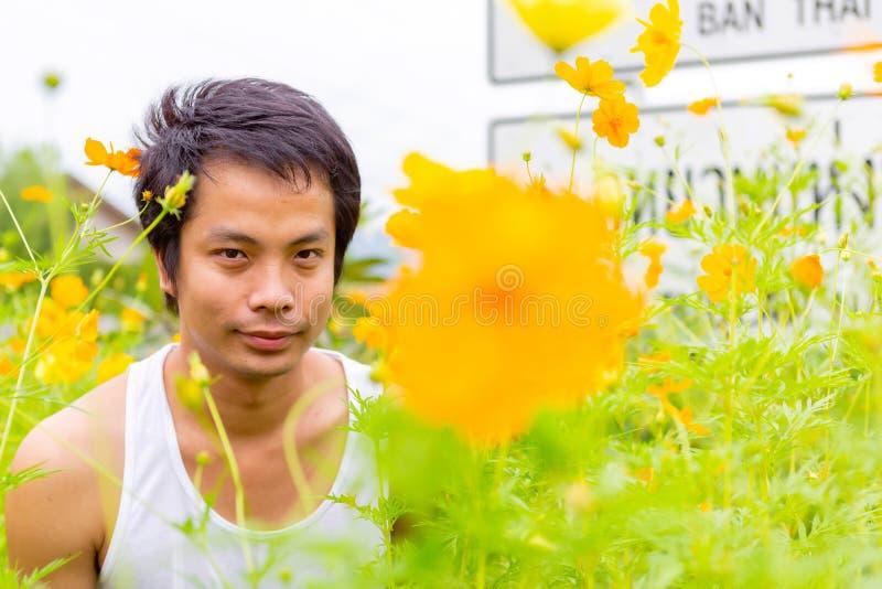 Homme thaïlandais dans la position blanche de dessus de réservoir dans le jardin jaune de cosmos photographie stock