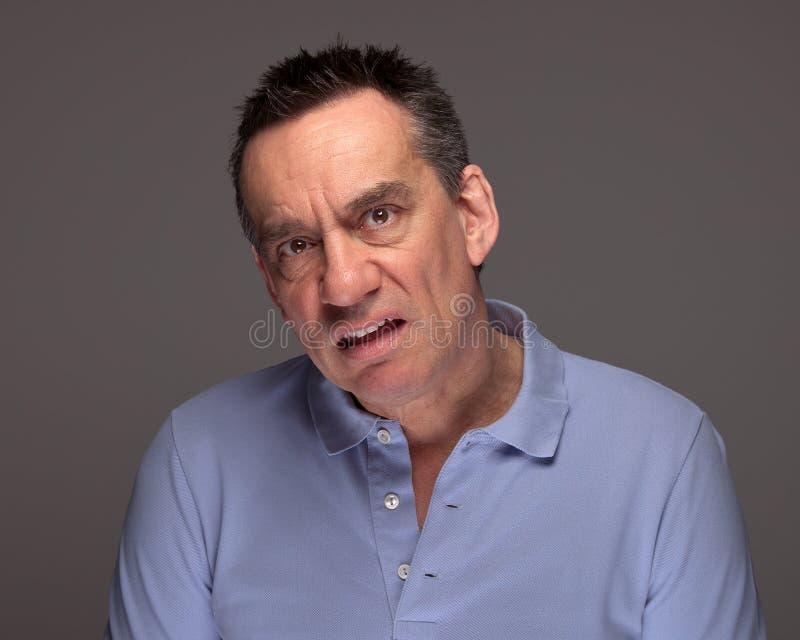 Homme tirant le visage semblant malheureux photos stock