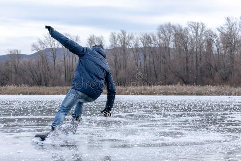 Homme tombant vers le bas tandis que patinage de glace Patins de neige de la dispersion en parties photographie stock