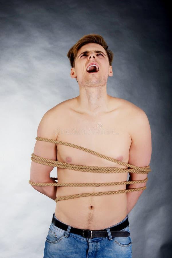 Homme torturé attaché avec une corde photographie stock