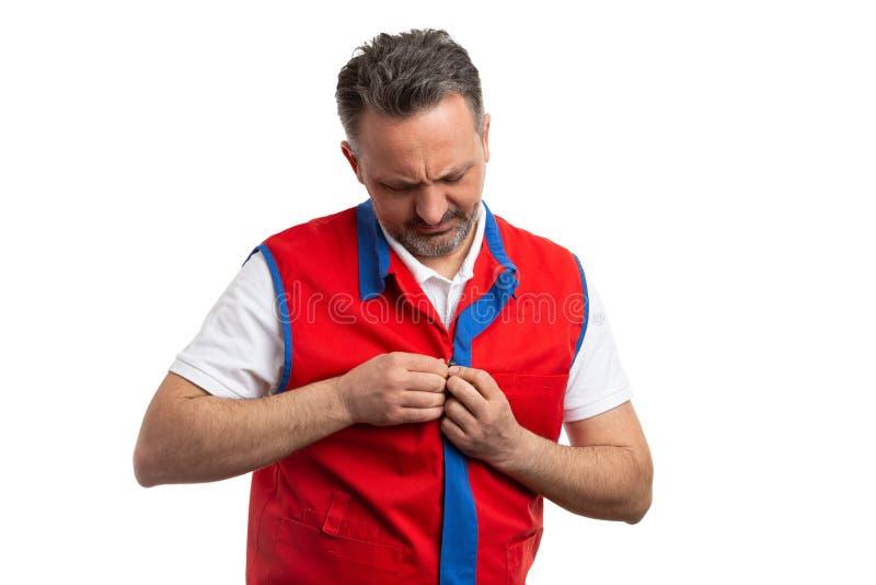 Homme travaillant à l'hypermarché boutonnant le gilet image stock