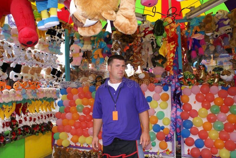 Homme travaillant à la foire ou au carnaval photographie stock libre de droits