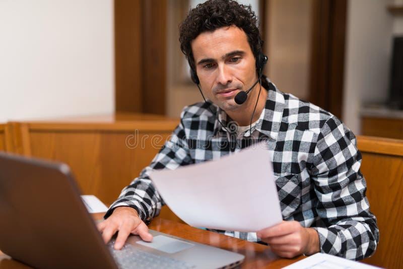 Homme travaillant à la maison avec son ordinateur portable photographie stock libre de droits