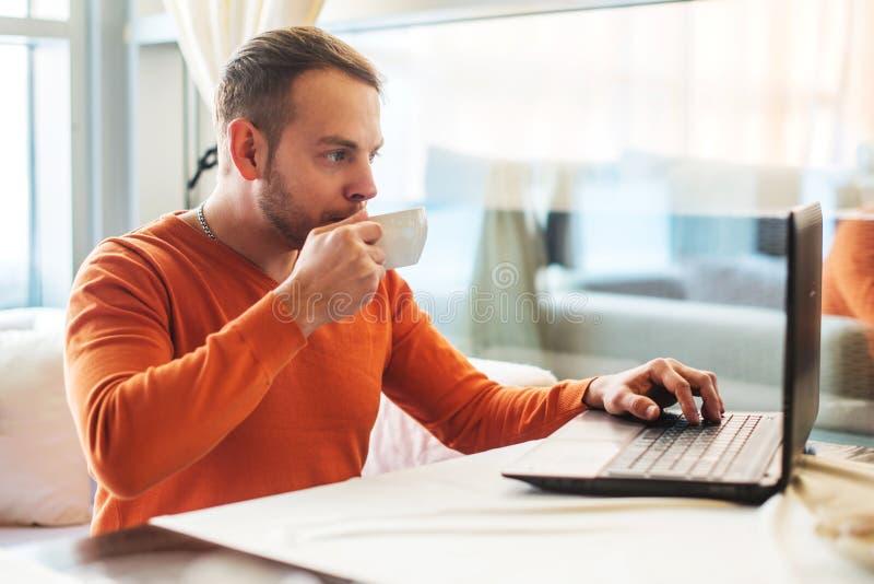 Homme travaillant au carnet en café image stock