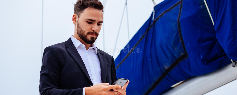 Homme travaillant au smartphone sur le yacht photos libres de droits