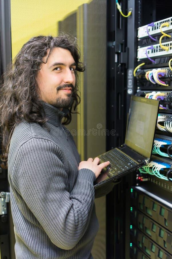 Homme travaillant avec des serveurs au centre de traitement des données image stock