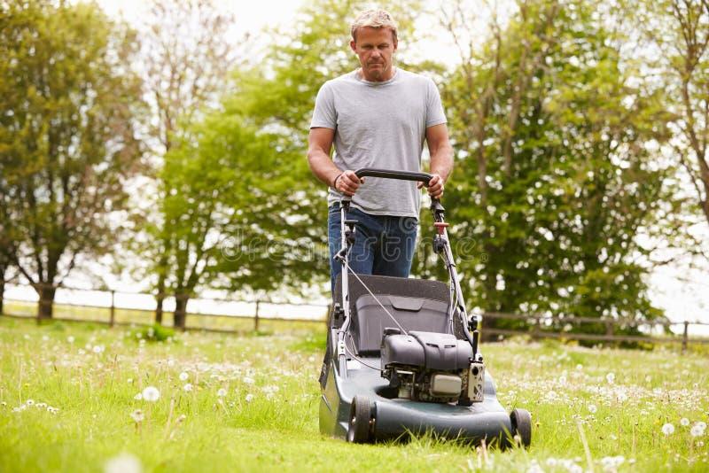 Homme travaillant dans l'herbe de coupe de jardin avec la tondeuse à gazon photographie stock libre de droits