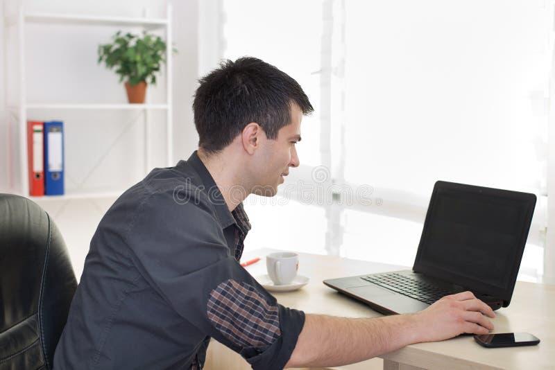 Homme travaillant sur l'ordinateur portable dans le bureau image libre de droits